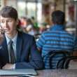 One relaxed young handsome professional businessman working with his laptop, phone and tablet in a noisy cafe. — Stock Photo #81254554