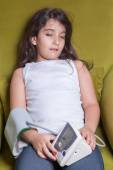 Small middle eastern girl feeling sick bad and holding digital blood pressure device. — Stock Photo