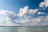 Lake and cloudscape and sailboat — Stock Photo