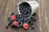 Blueberries and raspberries in a small bucket scattered on a woo — Stock Photo