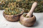 Mortier met stamper, olijf hout kom en droog gras hypericum. — Stockfoto