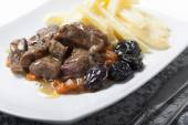 Stew with prunes, carrots and onions garnished with French fries — Stock Photo