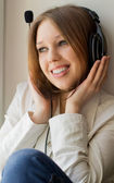Beautiful girl listen music near the window — Stock Photo