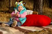Autumn, a little girl with a toy red heart — Stock Photo