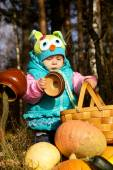Little girl playing with pumpkins on the nature — Stock Photo