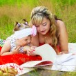 Mom with her daughter reading a book — Stock Photo #64071009