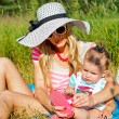 Modern mother sunning with baby on nature — Stock Photo #64071079