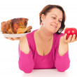 A complete woman is the choice of what to eat chicken or fruit — Stock Photo #64074637