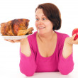 A complete woman is the choice of what to eat chicken or fruit — Stock Photo #64074649