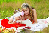 Mom with her daughter reading a book — Stock Photo