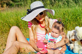 Modern mother sunning with baby on nature — Stock Photo