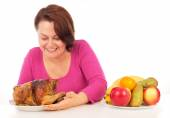 Full woman chooses what to eat — Stock Photo