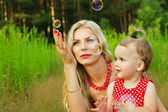 Happy mother and child with soap bubbles — Stock Photo