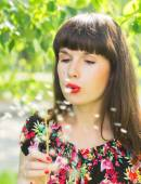 Happy girl blow on the dandelions — Stock Photo
