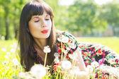 Happy girl blow on the dandelions — Stock Photo