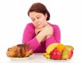 Full woman thinks to eat chicken or fruit — Stock Photo