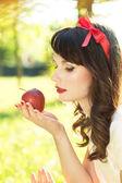 Beautiful Girl looks at Apple — Stock Photo