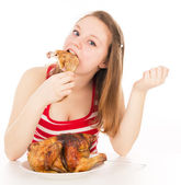 Girl greedily absorbing piece of chicken — Stock Photo