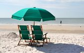 Green sun chairs and umbrella — Stock Photo