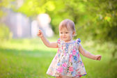 Little girl on a background of green leaves — Stock Photo