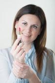Portrét mladé ženy použití rty tvoří — Stock fotografie