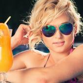 Girl with fresh orange juice in luxury pool — Stock Photo