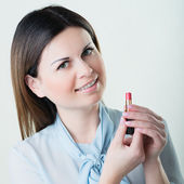 Portrait of young woman applying lips make up — Stock Photo