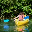 Two kids canoeing in a bautifull lake surrounded by green nature — Stock Photo #52698533