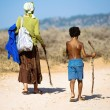 An old woman and a young boy walking along the dusty road — Stock Photo