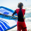 Closeup to a young man preparing to kitesurf — Stock Photo #52698567