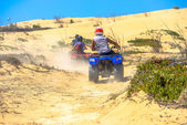 Two quads racing after one another in deserted dusty areas — Stock Photo