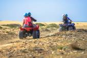 Two teams racing on quads towards the sea — Stock Photo