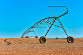 A big farming sprinkler out in the middle of wide field — Stock Photo