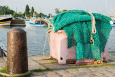 A big pile of fishing net in the harbor with ships and merry-go-round in the backgrouond — Stock Photo