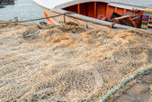 Huge fishing net spread on the ground next to a small boat — Stock Photo