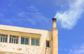 Upper floor of a building with ysmoke coming out of the chimney  — Stock Photo