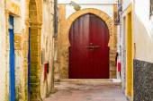 A beautiful arched red door at the end of a narrow street — Stock Photo