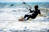 A sportive young man kitesurfing in the waves — Stok fotoğraf