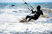 A sportive young man kitesurfing in the waves — Foto de Stock