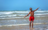 An elderly swimmer standing in the waves of the sea with his arms spread around — Stock Photo