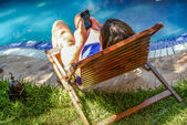 A young woman relaxing on a deck chair by the pool and messagin on her mobile phone — Stock Photo