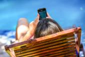 Closeup to young woman texting on her mobile phone while relaxing at the pool — Stock Photo