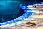 A curvy line of blue and while tiles circling the swimming pool — Stock Photo