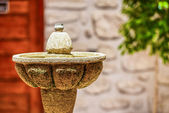 Top of the stone fountain on the background of brick wall — Stock Photo