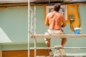 House painter in a street on a scaffolding — Stockfoto