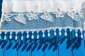 White lace curtains on a blue wooden shutter — Stock Photo