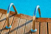 Blue swimming pool with teak wood — Stock Photo
