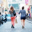 Two young ladies walking right in the middle of the street — Stock Photo #54585059