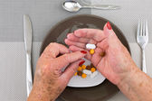 Red nailed elderly hands picking pills from a plate — Stock Photo