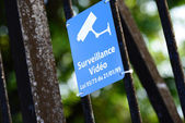 Blue sign of video surveillance fastened to metallic fence — Stockfoto